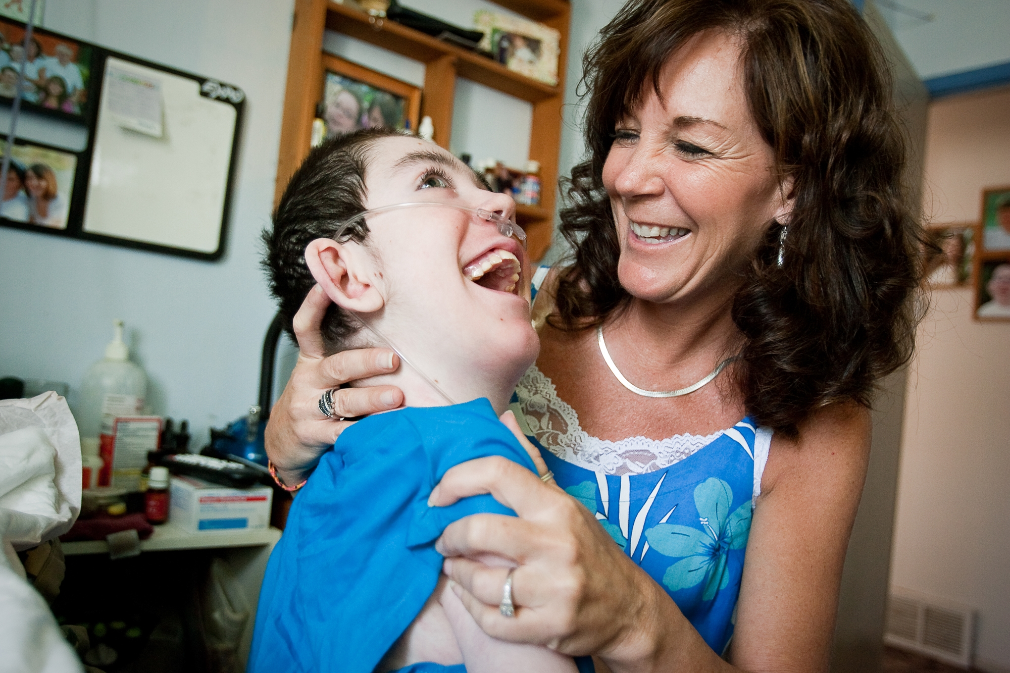 SHAWN GUST/Press Carla Schauer and her 12-year-old son Abe, who has Pelizaeus-Merzbacher Disease, laugh together while visiting Tuesday in their Post Falls home.  Local businesses worked together through the Wishing Star Foundation to donate a central air and heating system to the Schauer's, which will allow Abe to be in other rooms in his home.